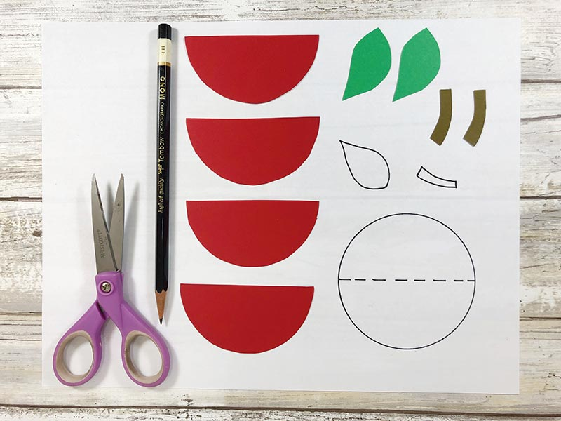 Purple handled scissors and pencil laying next to apple pieces cut out of cardstock paper next to craft pattern.