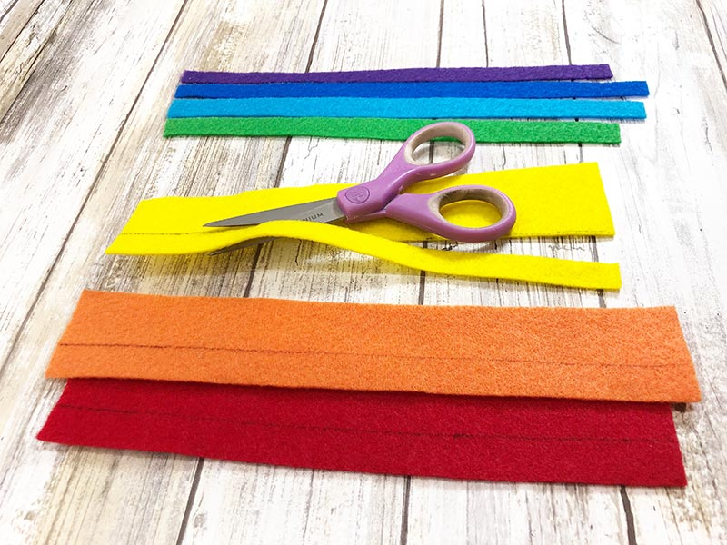 Scissors cutting strips of craft felt in assorted colors of the rainbow.