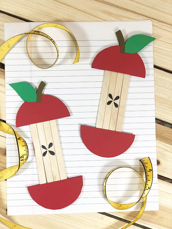Two red apple cores made with paper and popsicle sticks laying on loose leaf paper with a soft measuring tape curled around the edges.