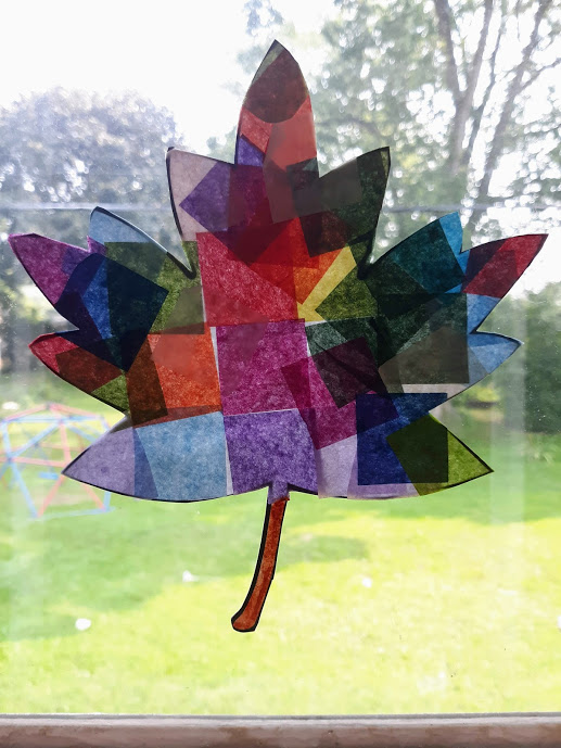 Finished multi-colored tissue paper leaf suncatcher craft hanging in sunny windown.