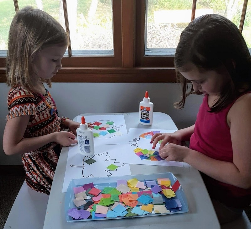 Two young white girls sitting across from each other at a table gluing tissue paper squares to the fall craft templates.