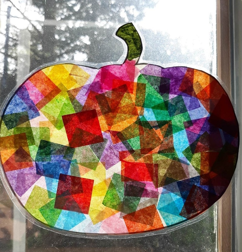 Close up of sun shining through tissue paper pumpkin suncatcher hanging in window.