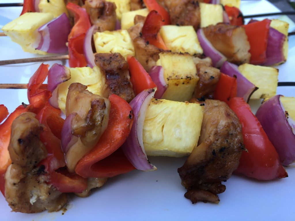 Close up view of cooked chicken shish kabobs with pineapple, red pepper, and red onion.