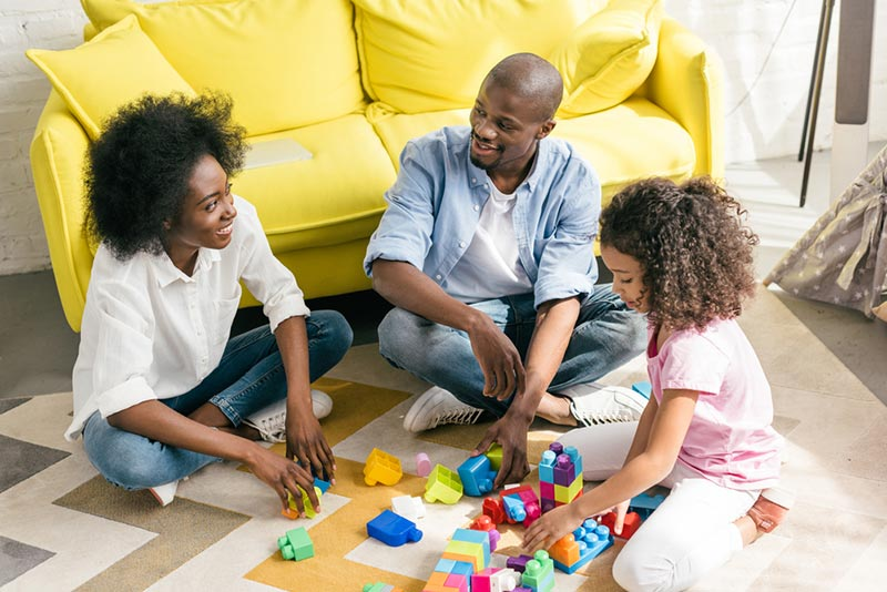 Happy Black family sitting on the floor together and playing with colorful blocks.