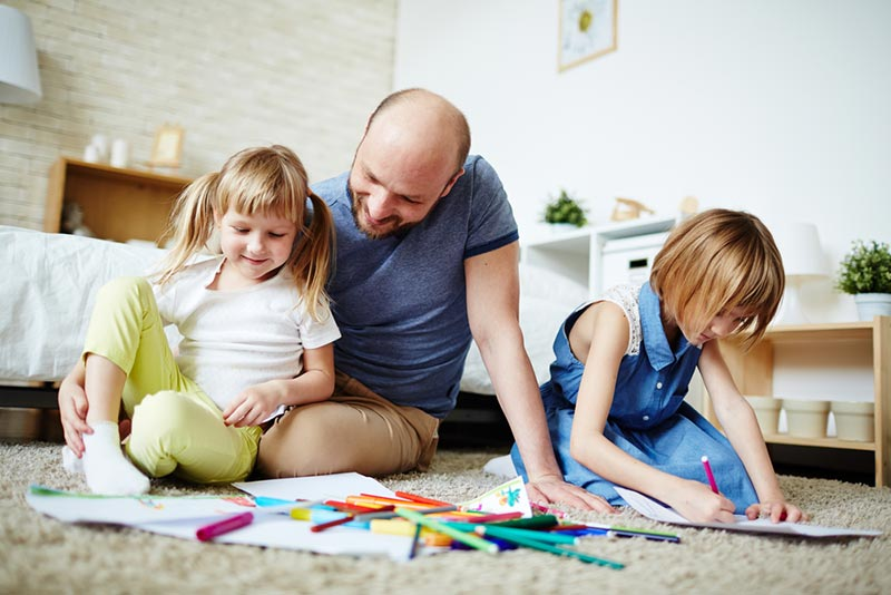 White dad sitting on floor with two daughters smiling and drawing.
