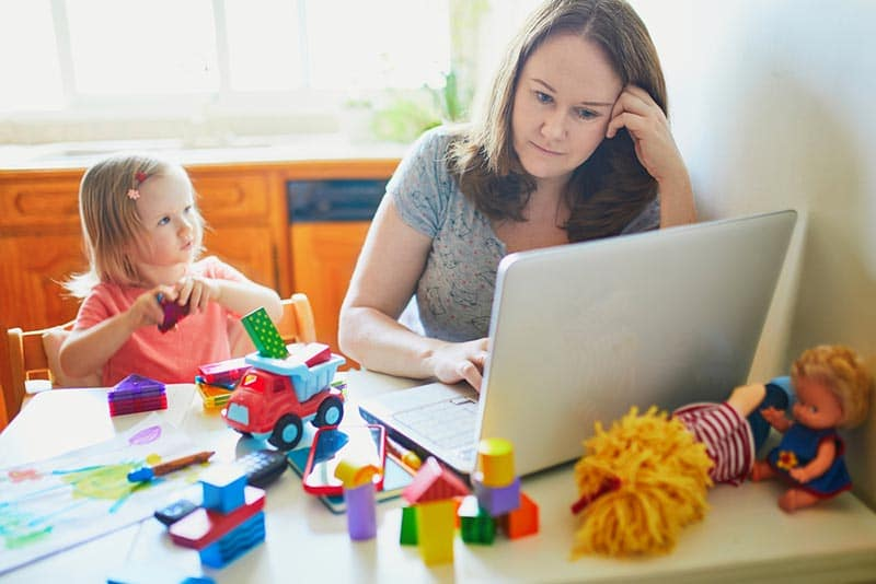 White mom working on laptop at the table with young child sitting next to her with toys all over table.