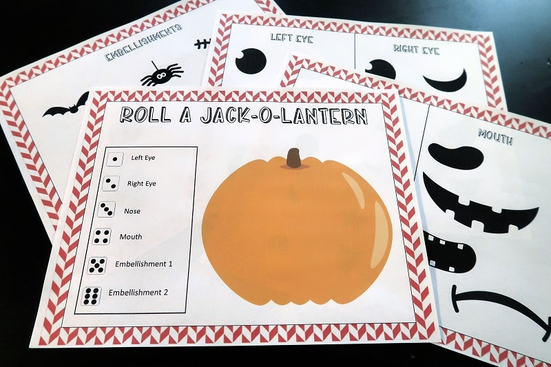 Blank pumpkin with dice key and other pages from printable game set on black table.