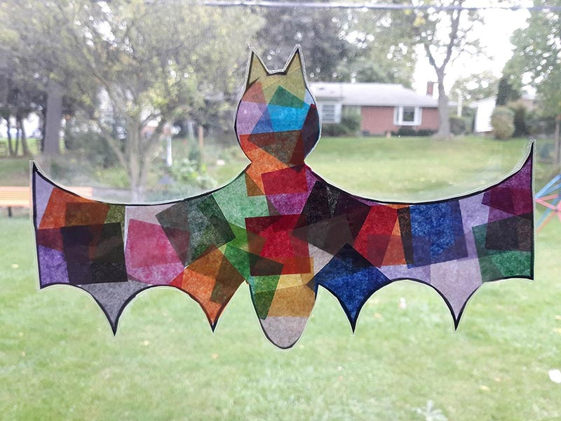 Halloween bat shaped paper suncatcher hanging in window looking into grassy backyard.