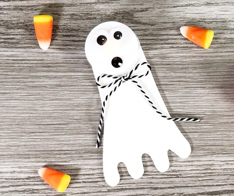 Overhead view of completed ghost tea light craft on gray wood background and three candy corn.