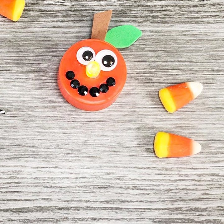 Finished Jackolantern pumpkin tea light craft with light on next to a couple pieces of candy corn on a gray wood background.