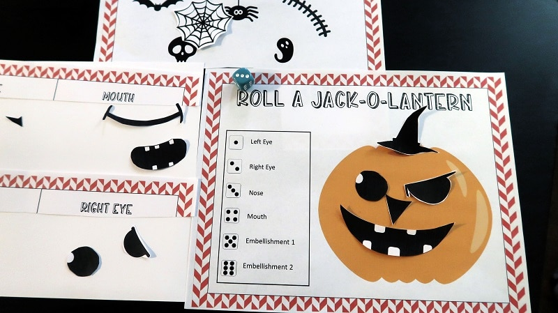 Roll a Jack-O-Lantern dice game printables on black table with blue die. Cut out eyes, nose and mouth piece arranged on pumpkin to make a face.