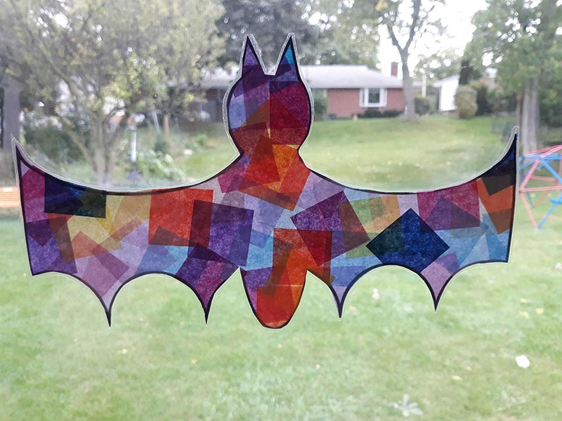 Colorful tissue paper makes bat look like faux stained glass suncatcher in window with grassy background.