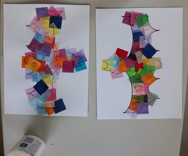 Overhead view of assorted colors of tissue paper squares glued to two print outs of bat template laying on table.