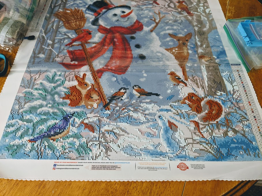 Happy snowman winter scene diamond art painting kit from Diamond Art Club on table with some rhinestone pieces applied along the bottom third of the canvas.