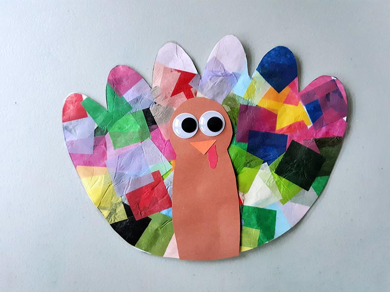 Completely assembled turkey tissue paper suncatcher craft laying on light gray table.