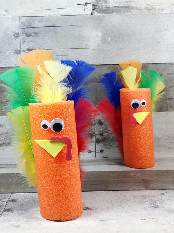 Two finished turkeys made out of orange pool noodles and different colors of craft feathers, one in the foreground and the other standing in the background.