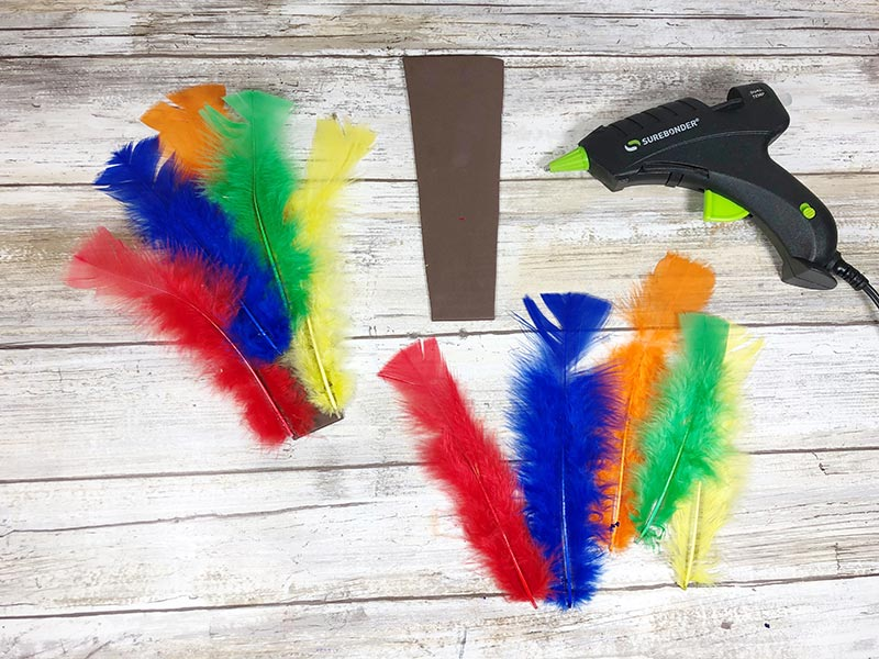 Assorted colors of craft feathers being hot glued to a piece of brown craft foam.