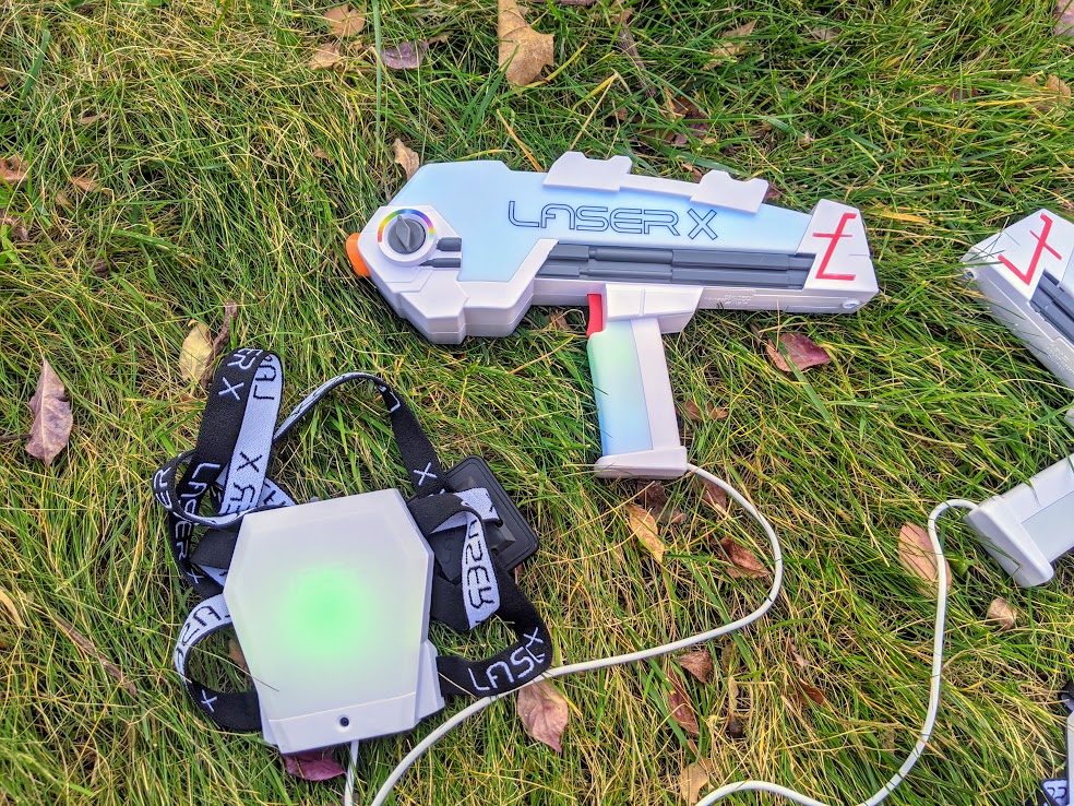Laser X Revolution blaster with green light on health indicator. Blaster laying in grass outside.