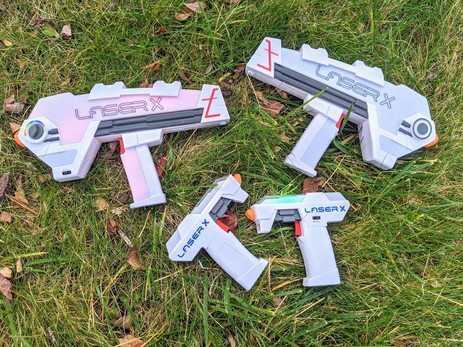 Pair of Laser X Evolution Blasters and a pair of Laser X Micro Blasters laying next to each other in the grass.