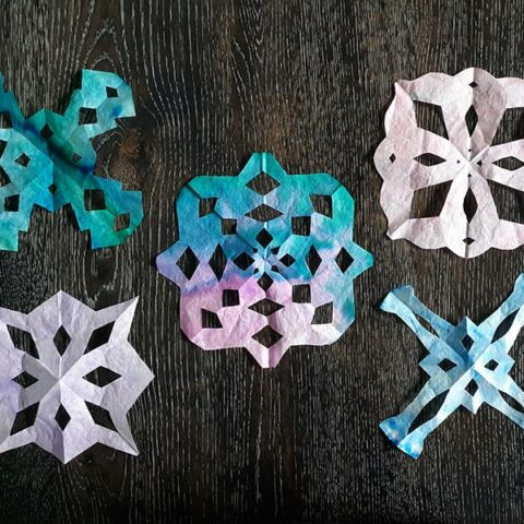 Overhead view of five finished coffee filter snowflake crafts cut in different shapes and patterns and in different colors laying on dark wooden table.