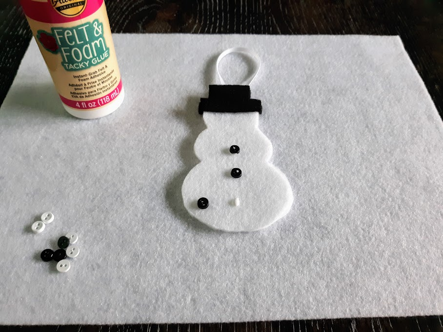 Felt snowman laying on white felt on table and gluing mini black buttons to the body.