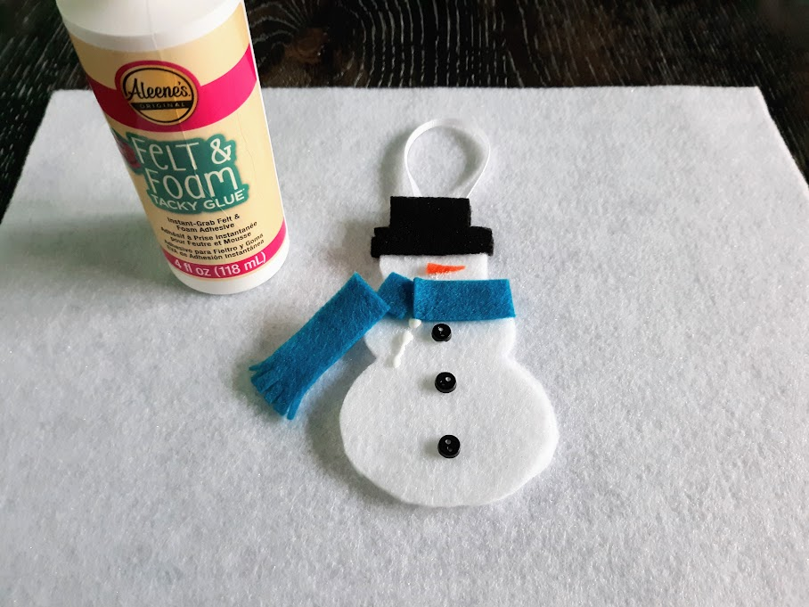 Gluing blue felt pieces to make scarf on snowman ornament