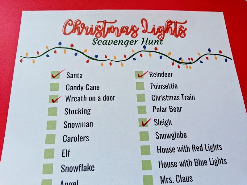 Close up view of printed out Christmas Lights scavenger checklist with a few items checked off with red marker.