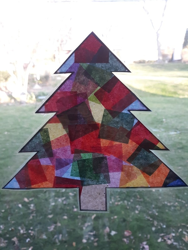 Finished evergreen tree shaped suncatcher made with tissue paper on window. Can see grass and leaves outside on the lawn.