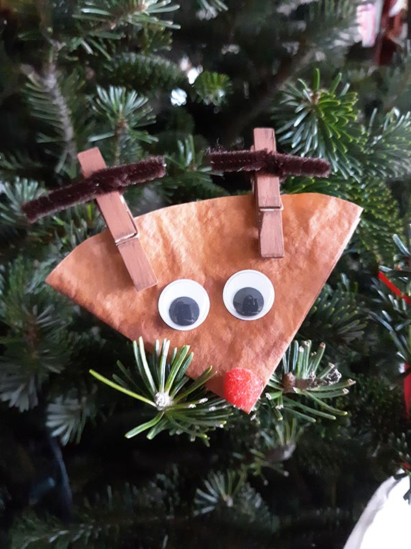 Close up of finished coffee filter reindeer craft displayed on Christmas tree.
