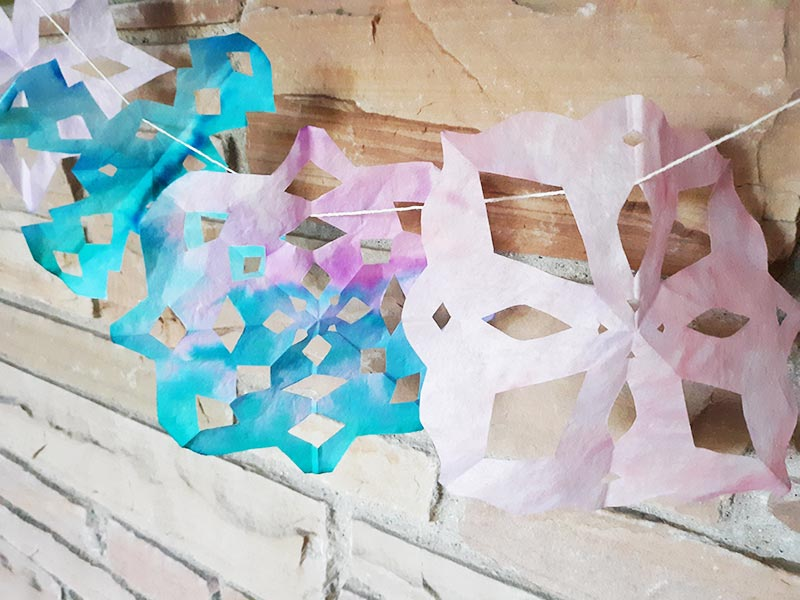 Angled view of several coffee filter snowflakes strung up as garland hanging from a brick fireplace mantel.