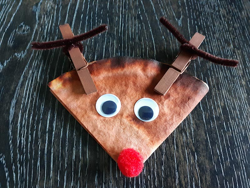 Completed coffee filter reindeer craft with googly eyes and clothespin antlers.