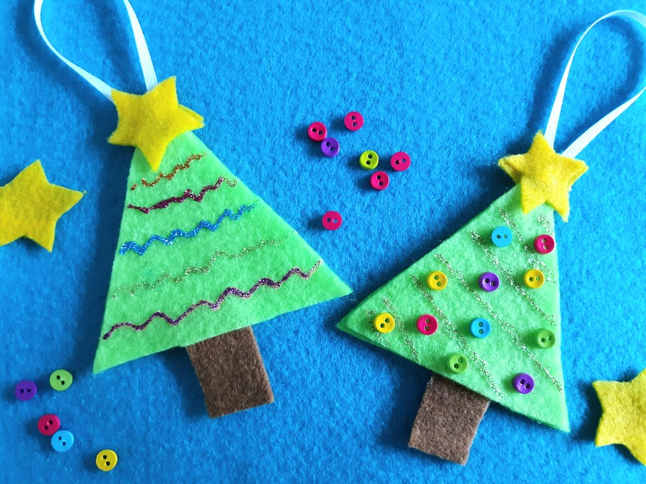 Overhead view of two Christmas tree felt ornaments. One decorated with lines of glitter glue and the other decorated with glitter glue and multicolored mini buttons. Ornaments laying on a blue felt background with stars and buttons scattered around.