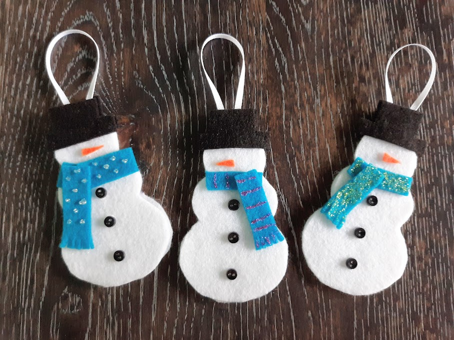 Overhead view of three completed felt snowman Christmas ornaments laying on dark wooden table.