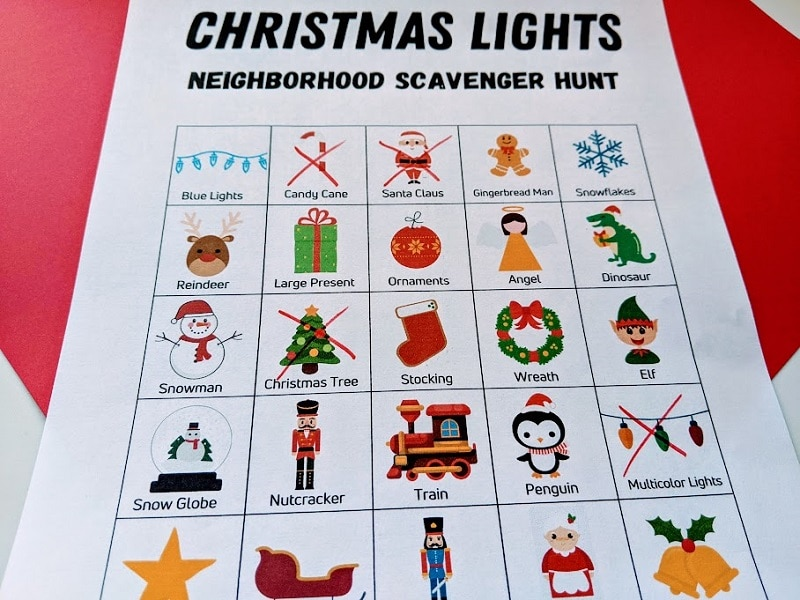 Close view of Christmas lights picture scavenger hunt page printed out with four different boxes crossed out with red marker.