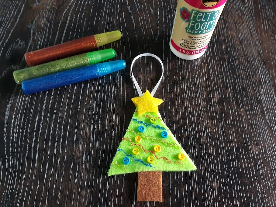 Decorated Christmas Tree ornament made out of felt laying on dark wooden table next to glitter glue pens and felt and foam tacky glue.