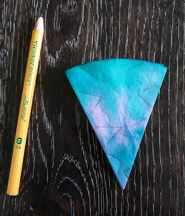 Pencil laying on dark wooden table next to blue, green, and pink tie dyed coffee filter folded like a triangle with lines drawn on it to show where to cut.