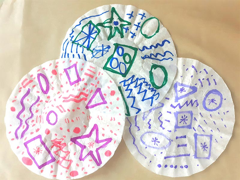 Three round coffee filter with a variety of designs drawn on them with markers laying overlapped on piece of parchment paper.