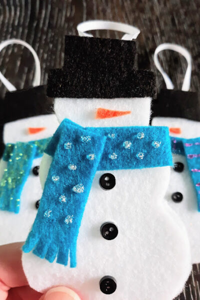Close up of white person's hand holding a completed felt snowman ornament with two more felt snowmen laying on table in background.