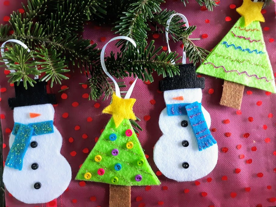 Two felt snowmen and two felt Christmas trees ornaments alternating in a row. Ribbon loops on evergreen branches with a red background.