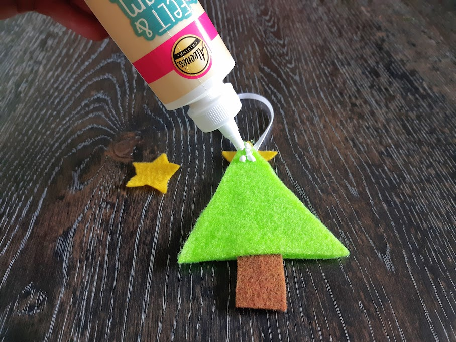Using felt and foam tacky glue to attach yellow felt star to top of felt Christmas tree ornament.