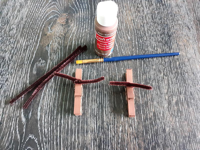 Two clothespins painted brown with brown chenille stems twisted around to make antlers. Also on table is bottle of brown paint, paint brush, and additional brown pipe cleaners.