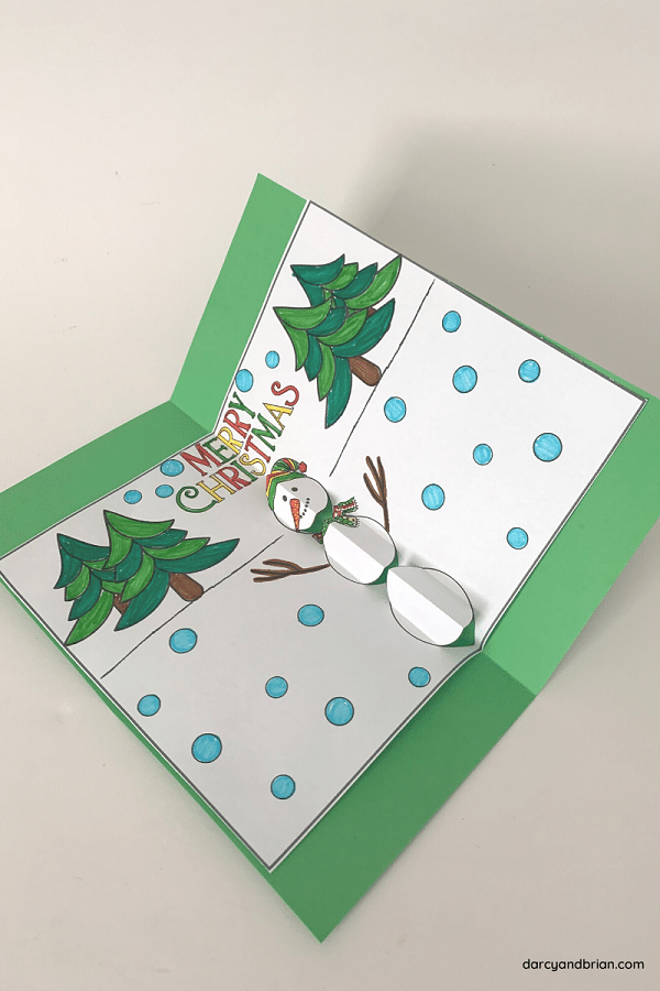 Finished pop up snowman card colored with markers and glued to green cardstock laying open at an angle on white background.
