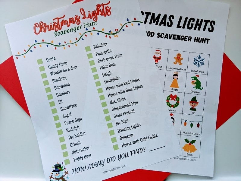 Two Christmas lights scavenger hunt pages printed out and laying overlapping each other on top of a piece of red cardstock.