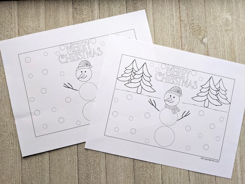 Snowman holiday card pages printed out and laying overlapped on gray wood background.