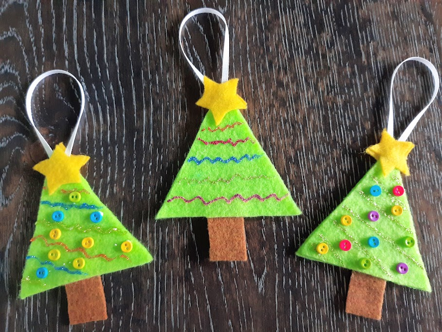 Three complete felt Christmas tree ornaments laying in a row on a dark wooden table.