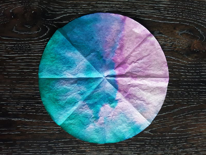 Round coffee filter tie dyed blue, green, and pink, laying on dark wooden table.