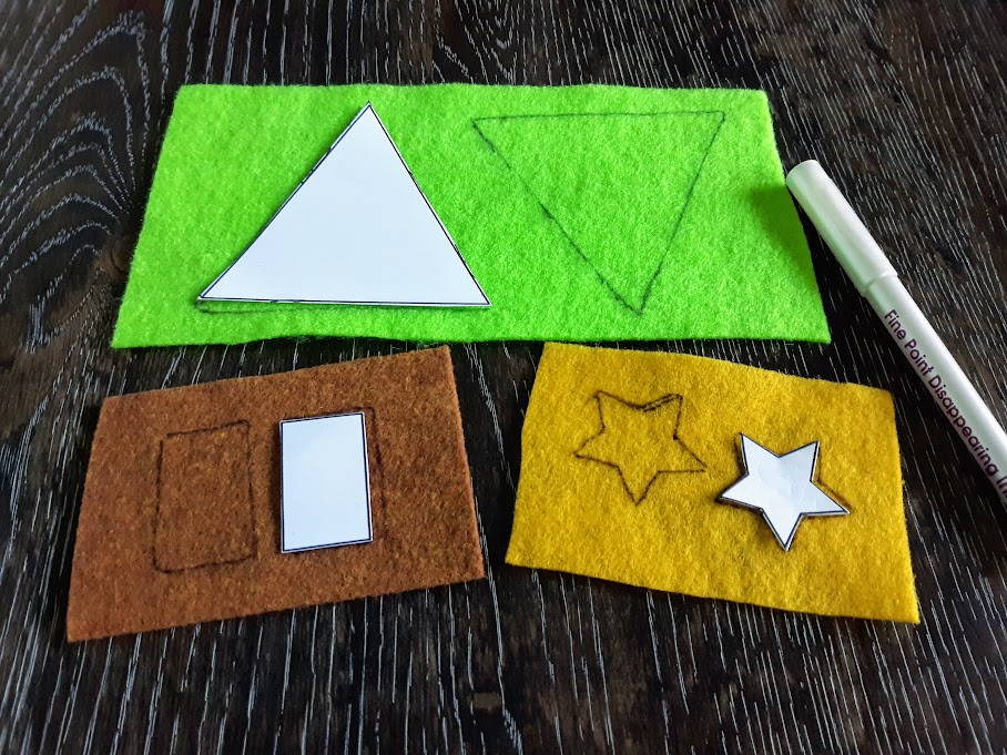 Printable templated being used to trace triangles on green felt, rectangles on brown felt, and stars on yellow felt.