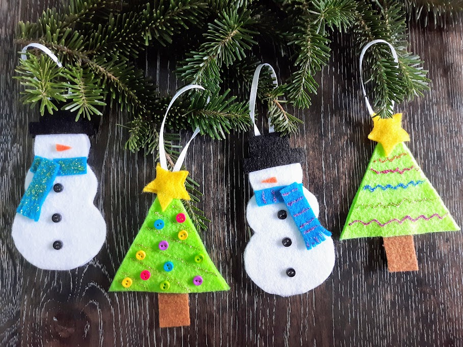 Four completed felt ornaments, alternating snowmen and Christmas trees. Ribbon is looped over evergreen branches. Background is a dark wood.