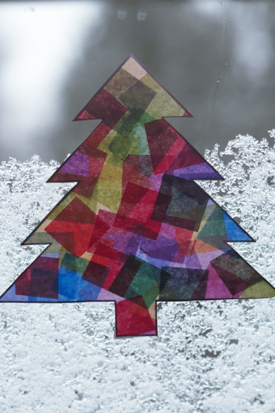 Close view of completed Christmas tree suncatcher hanging on snowy window.