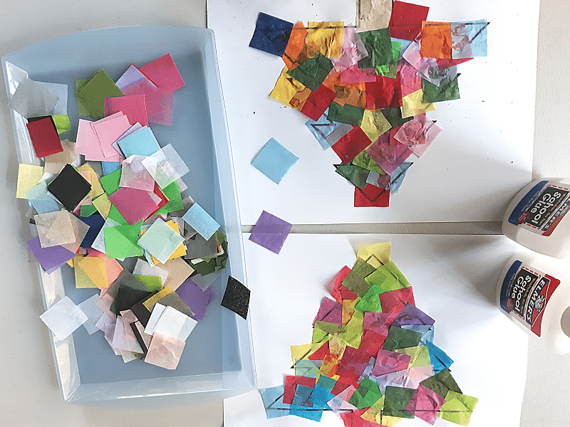 Light blue tray with assorted colors of pre-cut tissue paper squares next to two Christmas tree suncatcher templates covered with glued on tissue paper and two bottles of school glue.